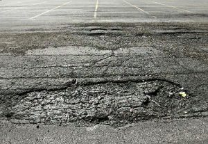what causes potholes in parking lot